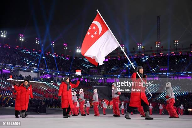 Flag bearer Cheyenne Goh of Singapore and teammates enter the stadium during the Opening Ceremony of the PyeongChang 2018 Winter Olympic Games at...