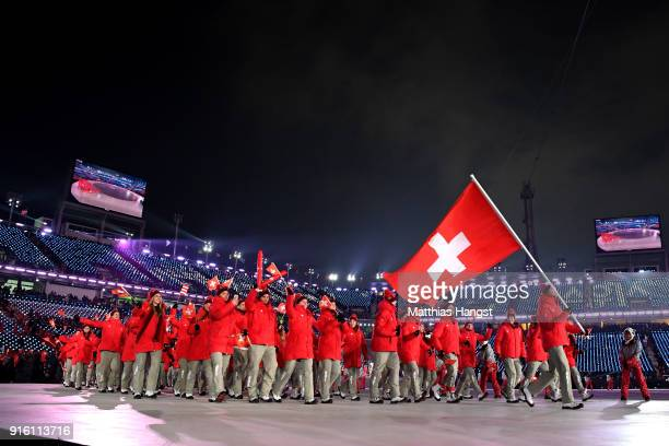 Flag bearer Dario Cologna of Switzerland and teammates enter the stadium during the Opening Ceremony of the PyeongChang 2018 Winter Olympic Games at...