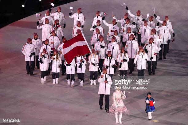 Flag bearer Daumants Dreiskens of Latvia and teammates enter the stadium during the Opening Ceremony of the PyeongChang 2018 Winter Olympic Games at...