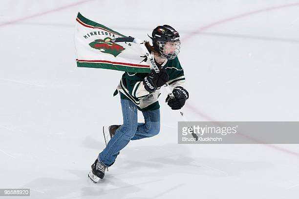 Flag Bearer Kate Rydland the granddaughter of NHL great Pat Quinn skates out onto the ice prior to the game between the Minnesota Wild and the...