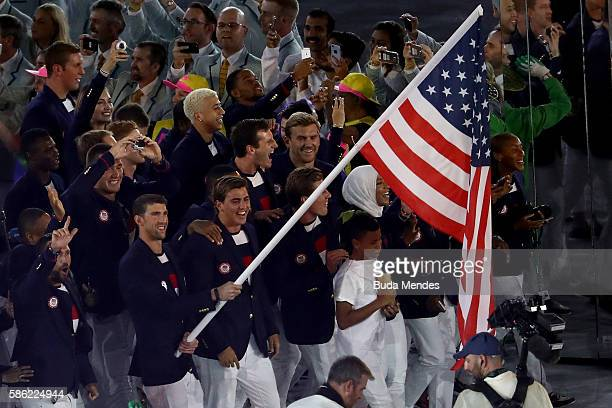 Flag bearer Michael Phelps of the United States and Ibtihaj Muhammad lead the US Olympic Team during the Opening Ceremony of the Rio 2016 Olympic...
