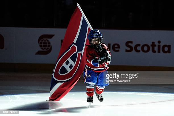 A flag bearer skates during pregame introductions prior to the during the NHL game between the Montreal Canadiens and theToronto Maple Leafs at the...