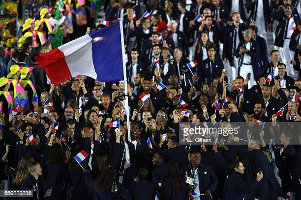 Flag bearer Teddy Riner of France leads his team during the Opening Ceremony of the Rio 2016 Olympic Games at Maracana Stadium on August 5, 2016 in...