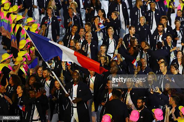 Flag bearer Teddy Riner of France leads his team during the Opening Ceremony of the Rio 2016 Olympic Games at Maracana Stadium on August 5 2016 in...