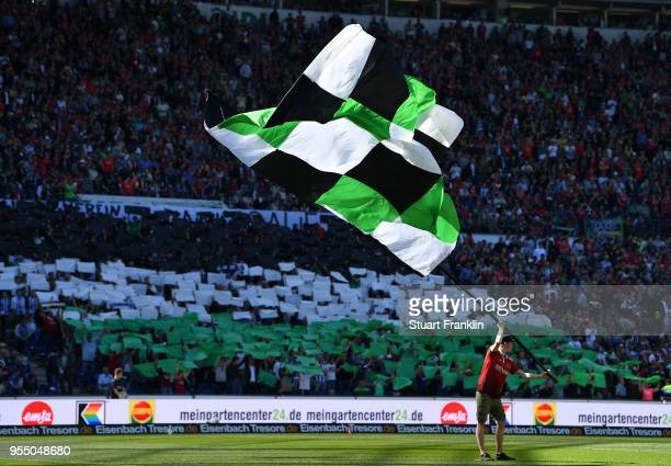 A flag bearer waves his flag before the Bundesliga match between Hannover 96 and Hertha BSC at HDIArena on May 5 2018 in Hanover Germany