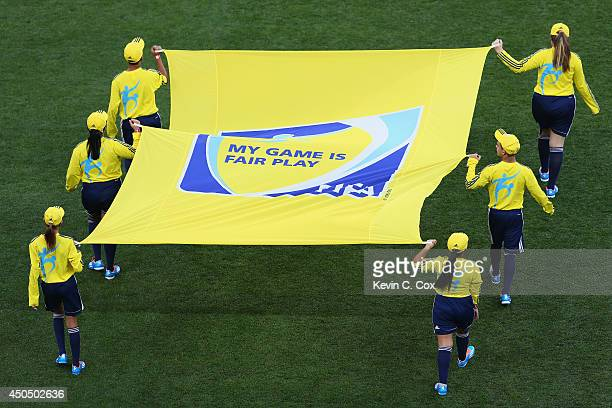 Flag bearers carry the FIFA flag before the 2014 FIFA World Cup Brazil Group A match between Brazil and Croatia at Arena de Sao Paulo on June 12 2014...