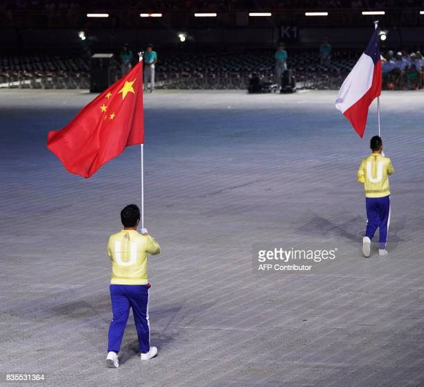Flag bearers carry the national flags of China and Chile during the opening ceremony of the 29th Summer Universiade Games at Taipei Municipal Stadium...