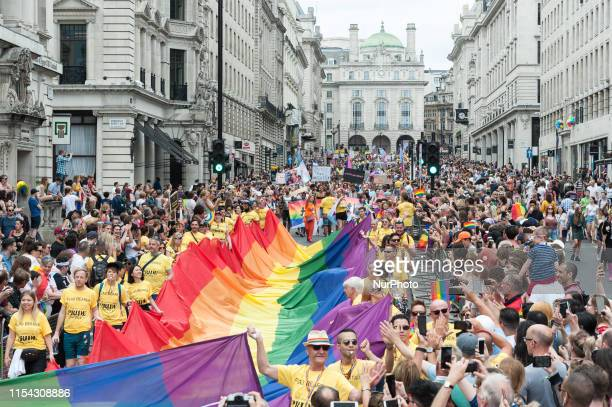 Flag bearers carry the rainbow flag during the Pride in London parade on 06 July 2019 in London England The festival which this year celebrates 50...