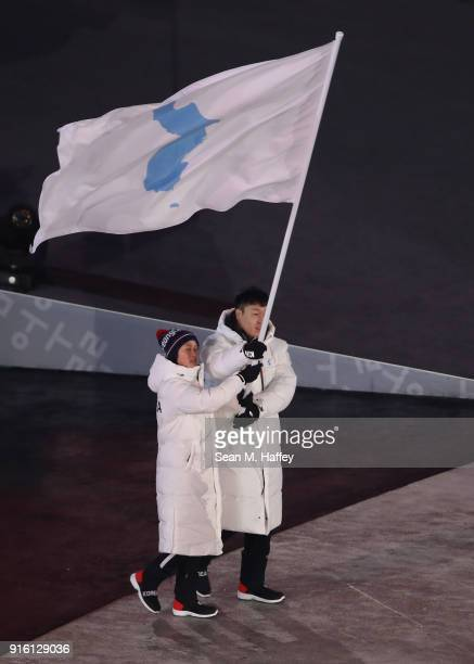 Flag bearers Chung Guam Hwang and Yunjong Won of Republic of Korea enter with the Korean Unification Flag during the Opening Ceremony of the...