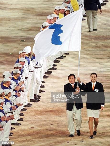 Flag bearers Jang Choo Pak of North Korea and EunSoon Chung of South Korea carry a special flag with the image of the Korean peninsula at the head of...