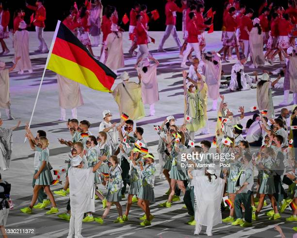 Flag bearers Laura Ludwig and Patrick Hausding of Team Germany lead their team out during the Opening Ceremony of the Tokyo 2020 Olympic Games at...