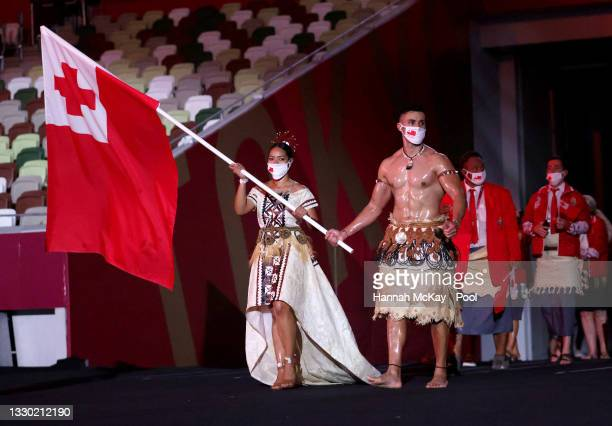 Flag bearers Malia Paseka and Pita Taufatofua of Team Tonga lead their team out during the Opening Ceremony of the Tokyo 2020 Olympic Games at...