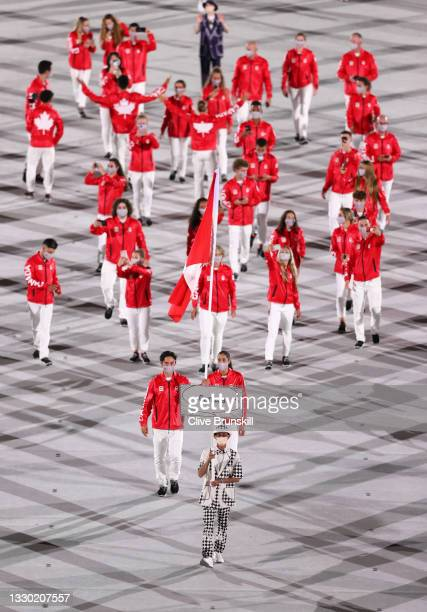 Flag bearers Miranda Ayim and Nathan Hirayama of Team Canada lead their team out during the Opening Ceremony of the Tokyo 2020 Olympic Games at...
