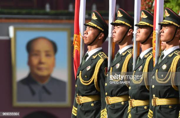 Flag bearers prepare for a welcome ceremony for Kazakhstan's President Nursultan Nazarbayev, near the portrait of late Chinese communist leader Mao...