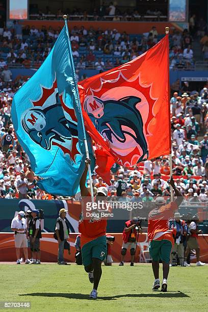 Flag bearers run with giant flags with the logo of the Miami Dolphins on them against the New York Jets at Dolphin Stadium on September 7 2008 in...