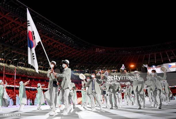Flag bearers Yeon Koung Kim and Sunwoo Hwang of South Korea lead their team out during the Opening Ceremony of the Tokyo 2020 Olympic Games at...