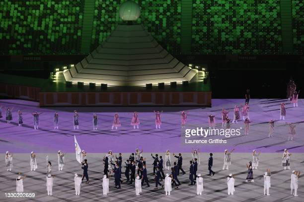 Flag bearers Yusra Mardini and Tachlowini Gabriyesos of The Refugee Olympic Team lead their team past the Olympic Cauldron during the Opening...