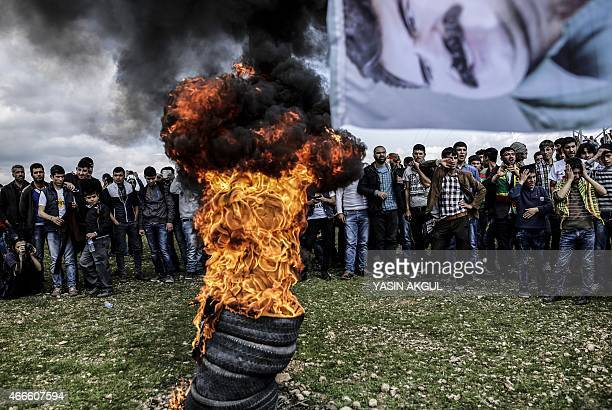 A flag bearing a portrait of jailed Kurdish leader Abdullah Ocalan flies near a fire as Kurdish people gather to celebrate Newroz which marks the...