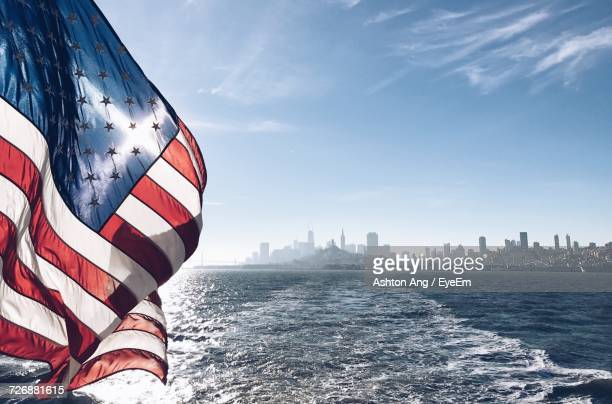 flag by cityscape against sky - american flag ocean stock pictures, royalty-free photos & images