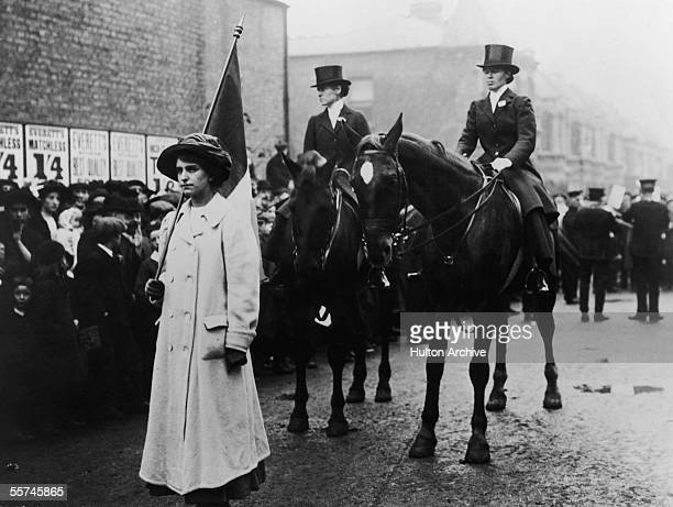 A flag carrier and two mounted marshalls in a suffragette march through London in support of the Women's Suffrage Bill June 1910 One of the riders is...