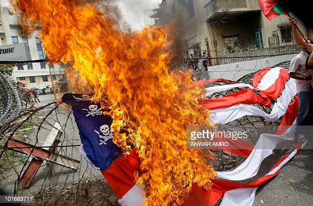 THE US flag drapped on barbed wire is set alight as several hundred leftwingers demonstrate near the US embassy in Awkar close to Beirut on June 6...