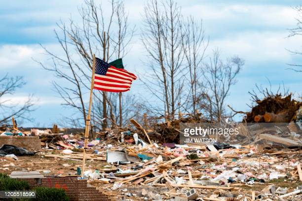 A flag flaps in the wind as US President Donald Trump tours tornado damage in Cookeville Tennessee on March 6 2020 At least 24 are dead in the wake...