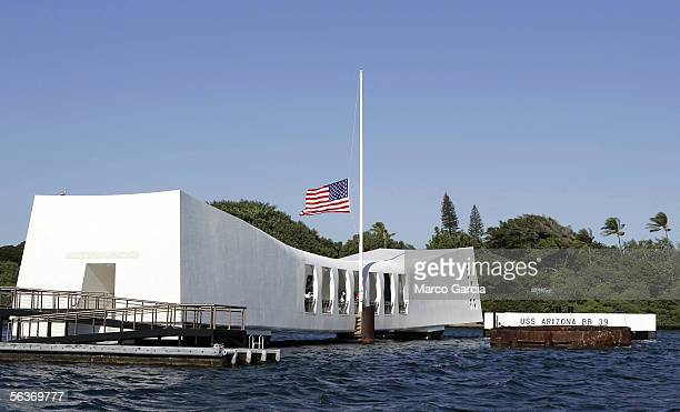S flag flies at half mast aboard the USS Arizona Memorial during the ceremony honoring the 64th anniversary of the surprise attack on Pearl Harbor...