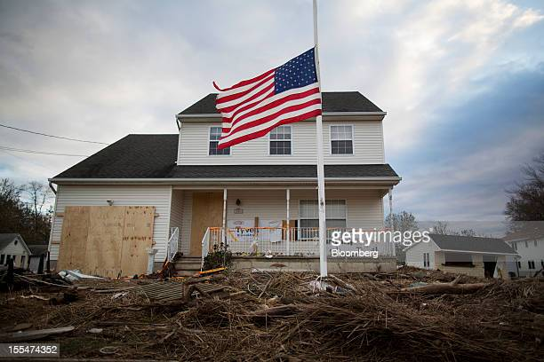 A flag flies at half mast as debris from houses destroyed during Hurricane Sandy clog streets and yards in Union Beach New Jersey US on Saturday Nov...