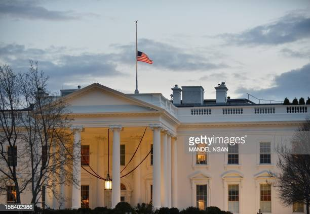 A US flag flies at halfstaff above the White House on December 15 2012 in Washington DC Twentyseven people including the shooter were killed Friday...