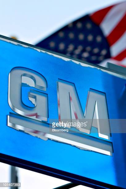 Flag flies behind a peeling General Motors Co. Logo outside the company's headquarters building in Detroit, Michigan, U.S., on Tuesday, June 1, 2010....