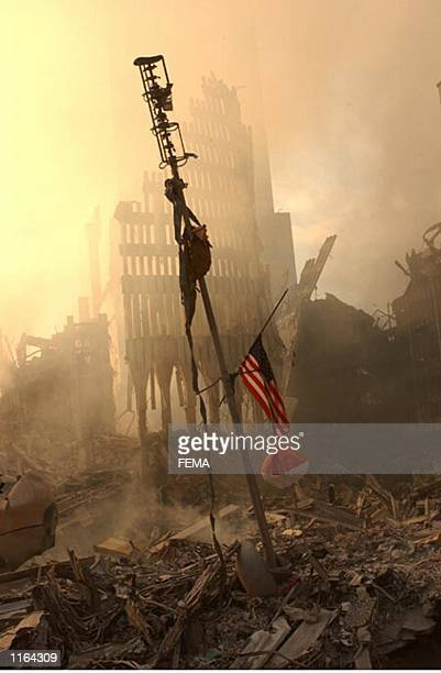 Flag flies from a television antenna September 13, 2001 amid the rubble of the World Trade Center after an aircraft crashed into it September 11 as...