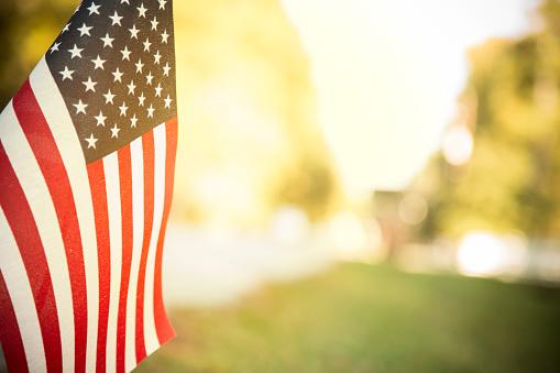 USA flag flies in afternoon sun along neighborhood road. 932322632