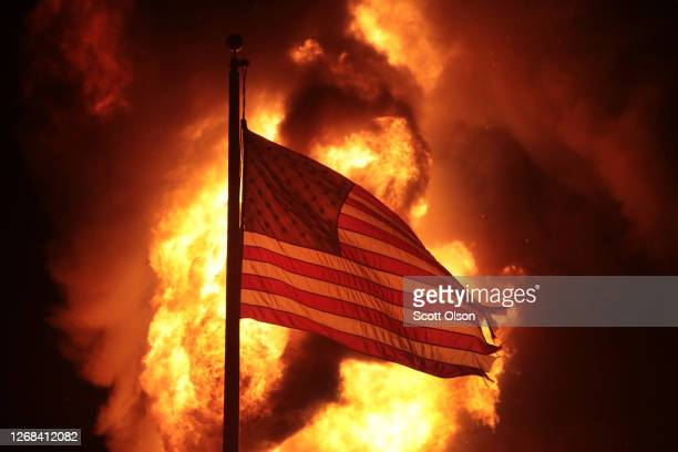 A flag flies in front of a department of corrections building after it was set ablaze during a second night of rioting on August 24 2020 in Kenosha...