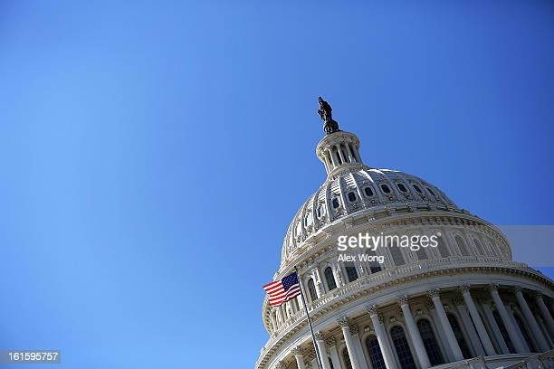 S flag flies in front of the dome of the US Capitol February 12 2013 on Capitol Hill in Washington DC US President Barack Obama will give his annual...