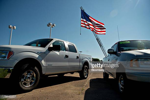 A US flag flies over Ford Motor Co vehicles at the Bill Walsh Ford car dealership in Ottawa Illinois US on Tuesday Sept 3 2013 Domestic and total...