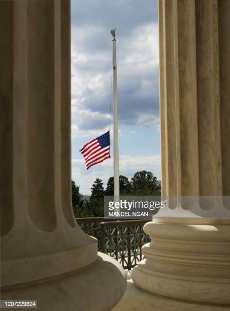 A US flag flying at half mast is seen between the colums of the Supreme Court following the death of chief justice William Rehnquist 04 September...