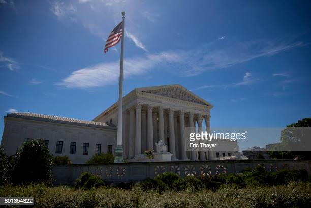 A flag flys outside the US Supreme Court after it was announced that the court will allow a limited version of President Donald Trump's travel ban to...