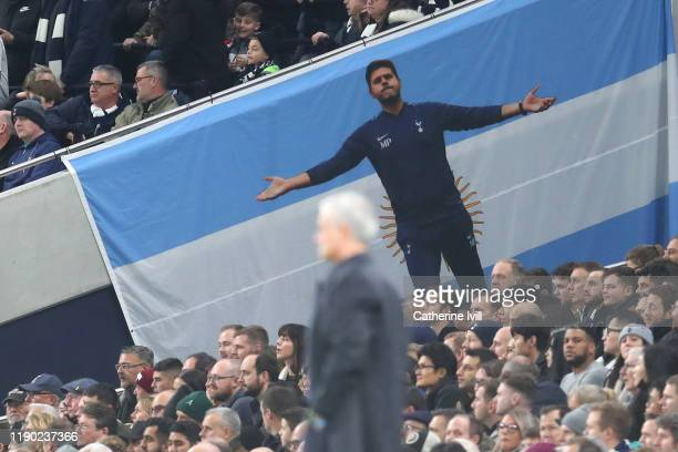 A flag for former Tottenham Hotspur manager Mauricio Pochettino is displayed in the crowd as Jose Mourinho Manager of Tottenham Hotspur looks on...