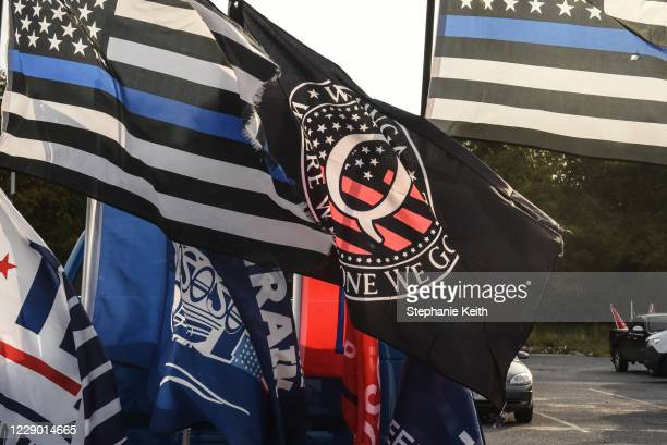 Flag for the QAnon conspiracy theory is flown with other right wing flags during a pro-Trump rally on October 11, 2020 in Ronkonkoma, New York. With...