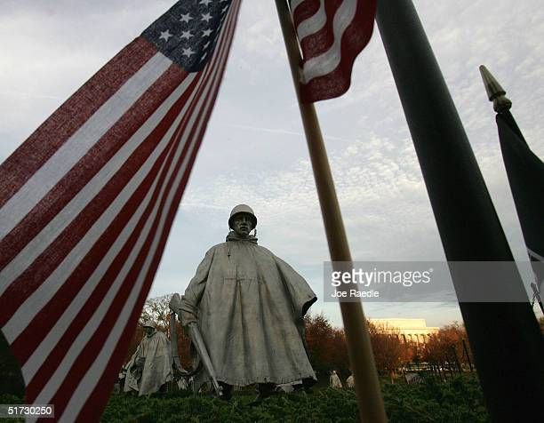 S flag frames a statue from the Korean War memorial on Veterans Day as visitors pay their respects to the soldiers killed during the war November 11...