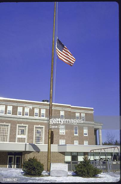 Flag halfmast at high school where teacher in space Sharon Christa McAuliffe taught after her death in Challenger disaster with plaque engraved with...