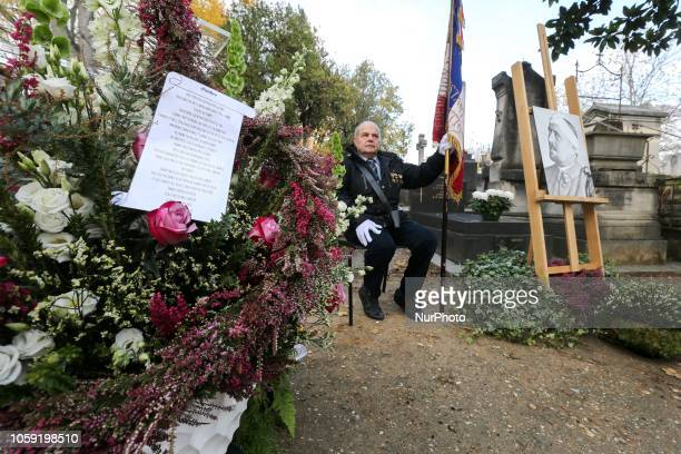 A flag holder stays near the French poet Guillaume Apollinaires portrait during a ceremony held on Novembre 8 at the grave of the poet at Père...