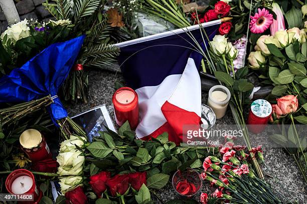 A flag in the french national colors lies between flowers at the gate of the French Embassy following the recent terror attacks in Paris on November...