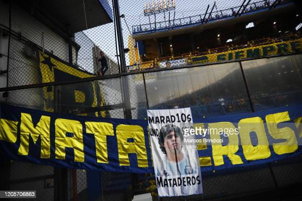 A flag is displayed with a photo of Diego Maradona former Boca Juniors player and coach of Gimnasia y Esgrima La Plata before a match between Boca...