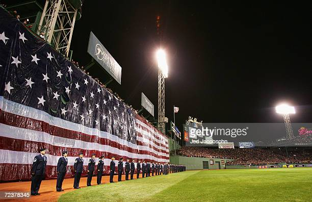 """Flag is draped over the """"Green Monster"""" during the singing of the National Anthem before game one of the World Series against the Boston Red Sox on..."""