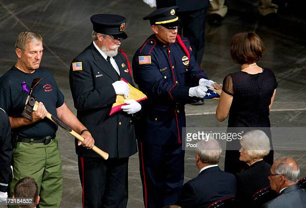 A flag is presented to Juliann Ashcraft widow of fallen firefighter Andrew Ashcraft during a memorial service honoring 19 fallen firefighters at...