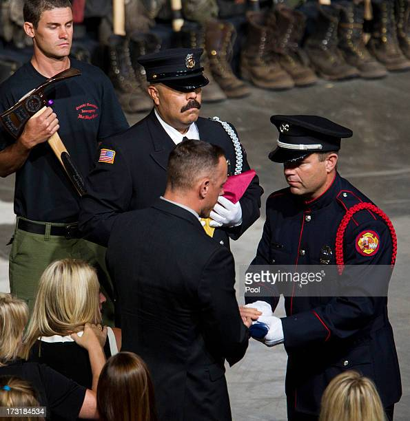 A flag is presented to the family of fallen firefighter Jesse Steed during a memorial service honoring 19 fallen firefighters at Tim's Toyota Center...