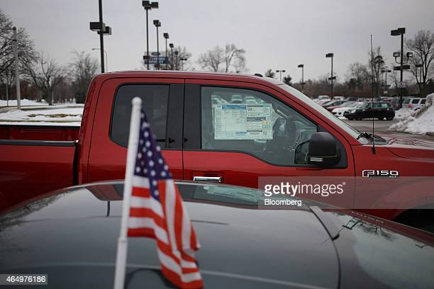 A US flag is seen on a vehicle next to a 2015 Ford Motor Co F150 truck displayed for sale at the Oxmoor Ford car dealership in Louisville Kentucky US...