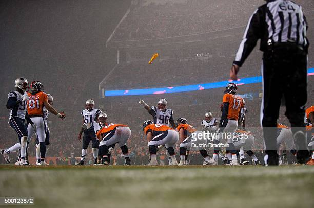 A flag is thrown and defensive tackle Sealver Siliga of the New England Patriots points at tight end Owen Daniels of the Denver Broncos after a false...