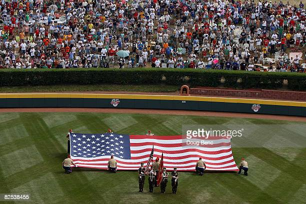 A flag is unfolded during the National Anthem before the United States takes on Mexico during the Little League World Series Championship game at...